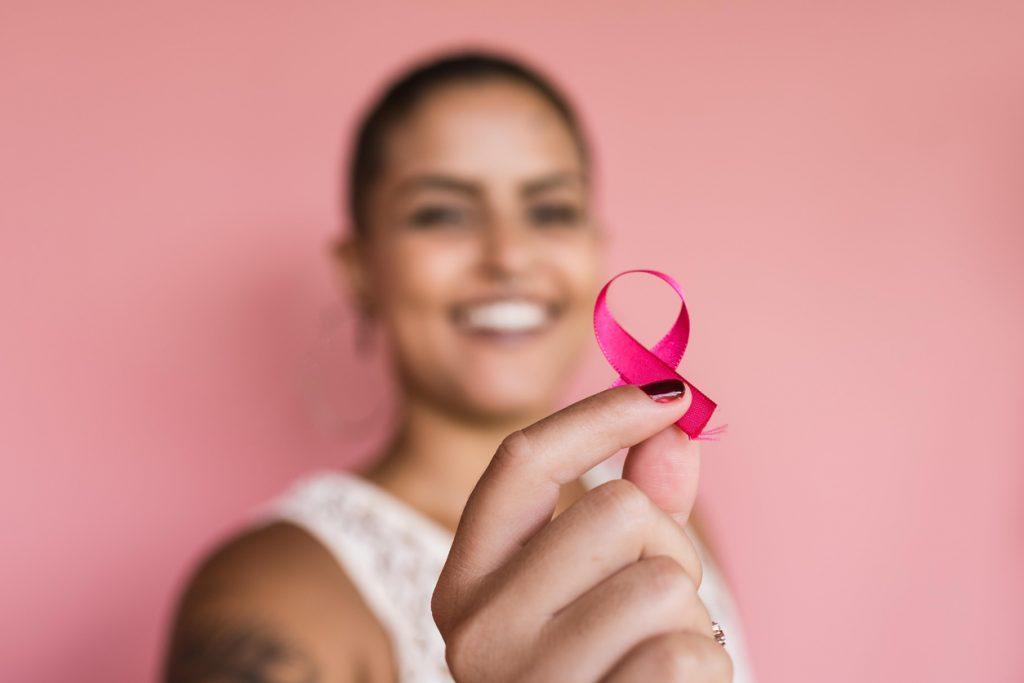mulher negra segurando laço outubro rosa